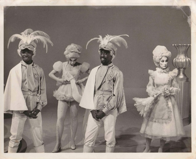 Bruce Heath and dancers are dressed in feather hats and elaborate costumes on the set of a 1970s television show