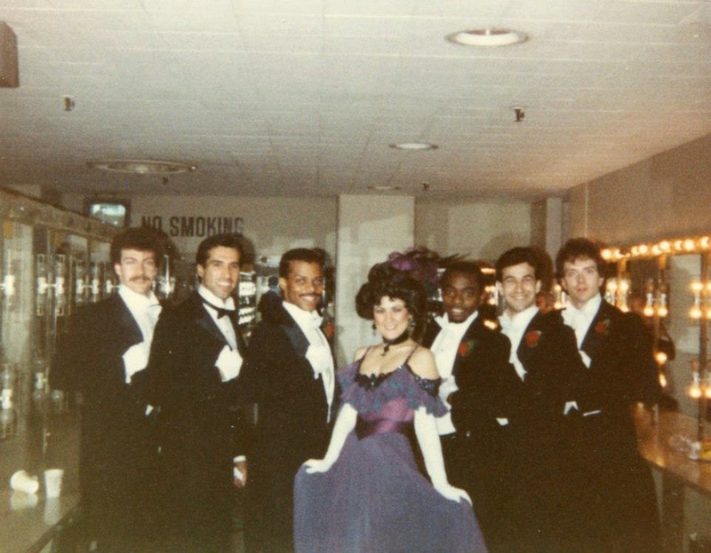 Bruce Heath in a tux along with other performers pose backstage of the Academy Awards