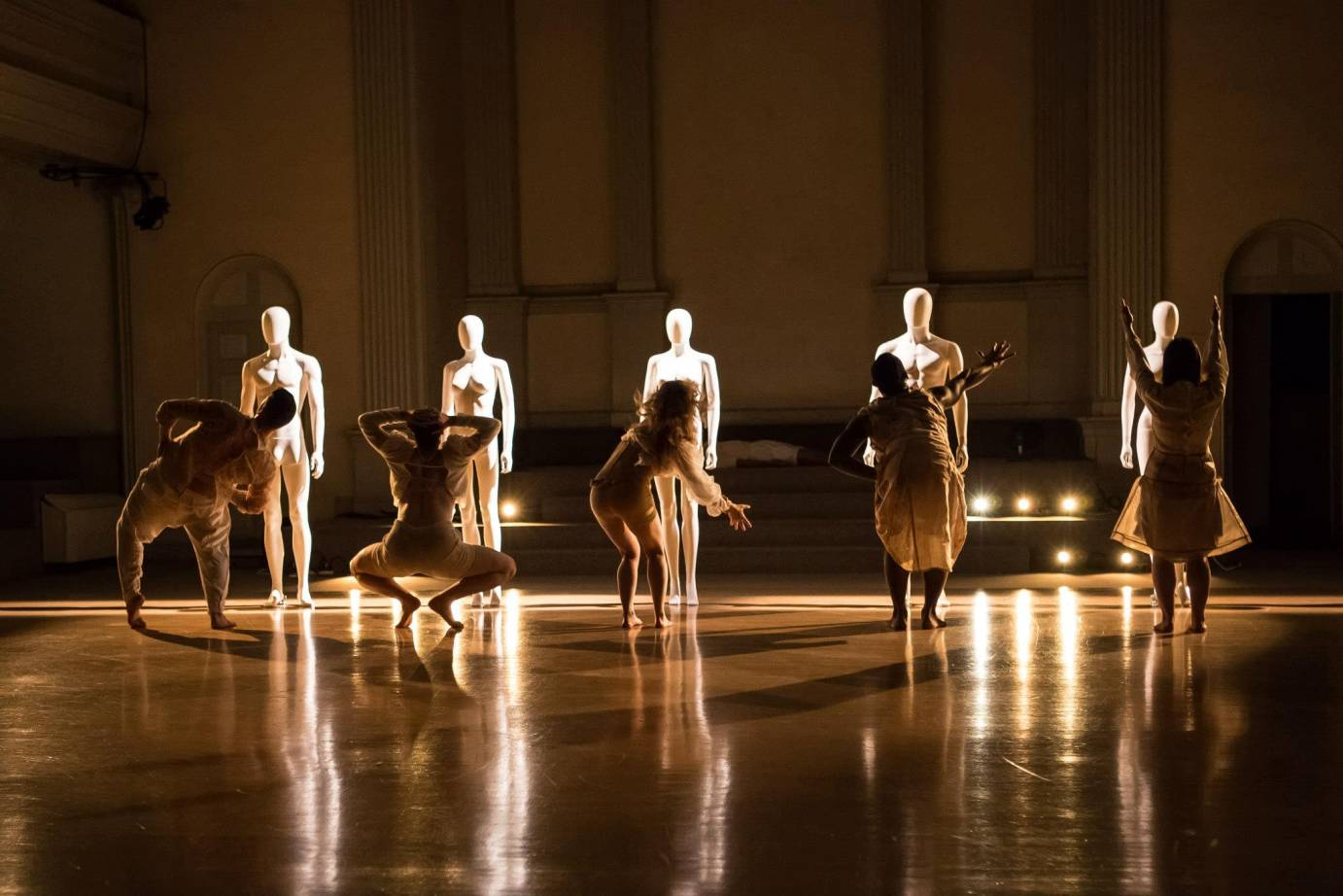Each dancer gestures to their mannequin counterpart; their backs are towards the audience