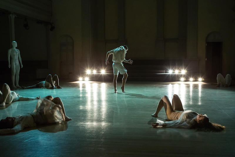 Dancers lay on their back as another male dancer in white strikes a standing pose with his fingers splayed