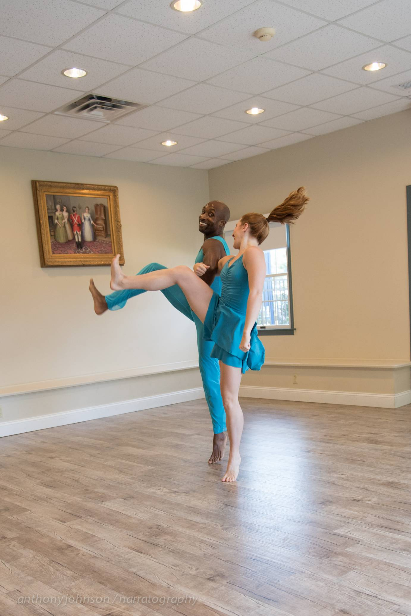 Two dancers perform in a stark gallery space. They wear bright blue costumes as they smile at one another.