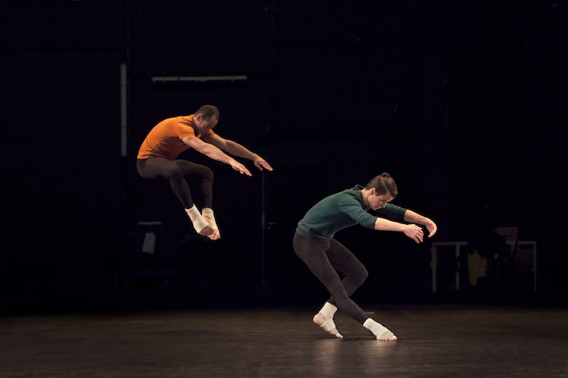 One dancer contracts his torso and pulls his torso back. Another dancer creates a similar a space except that he's jumping.