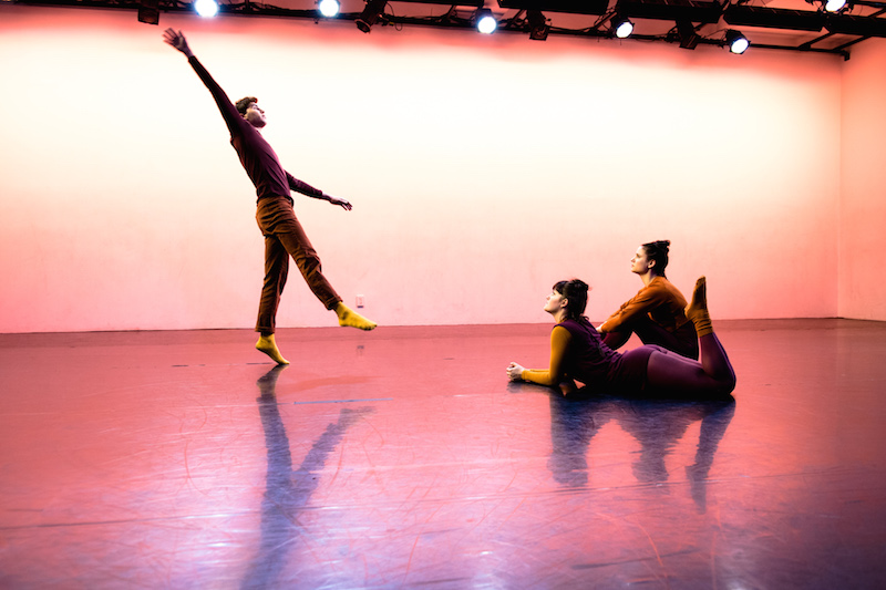 Two female dancers sit on the floor and look up at a male dancer perform. He balances on one leg as his right leg dangles in the air and his right arm extends to the ceiling