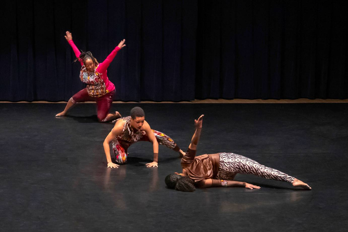 Three dancers range from lying to kneeling in a diagonal line