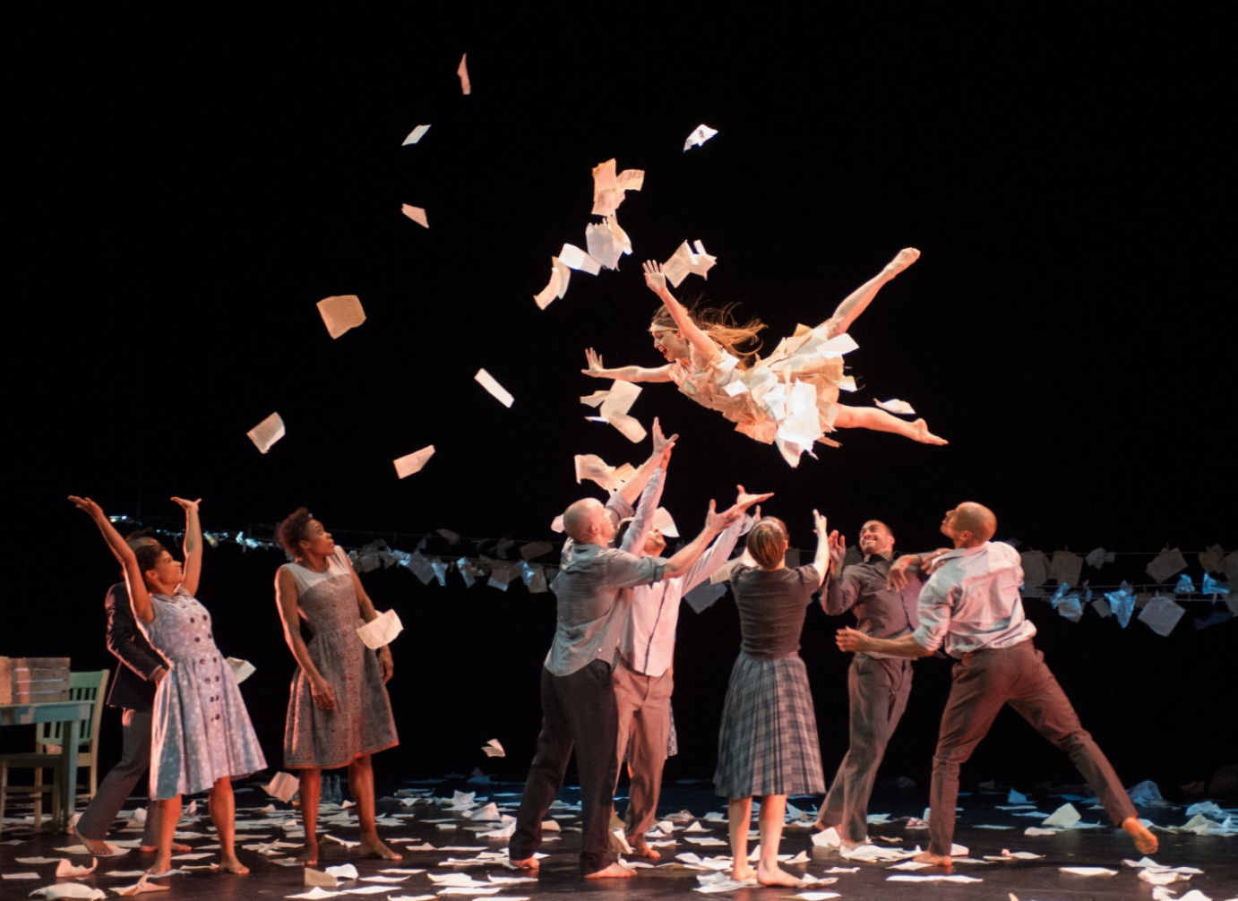 dancer flying through the air as paper sheets fly and hang in the background on a close line