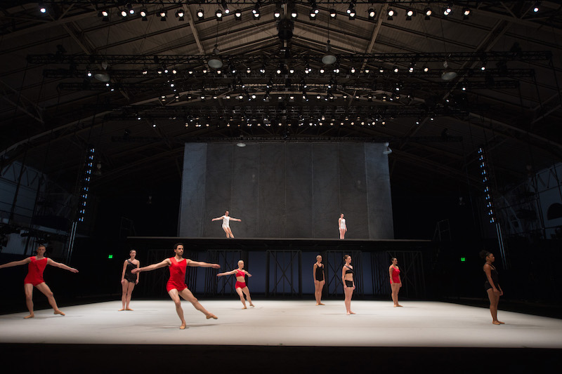 Dancers in black, white and red unitards perform on the first and above stages.