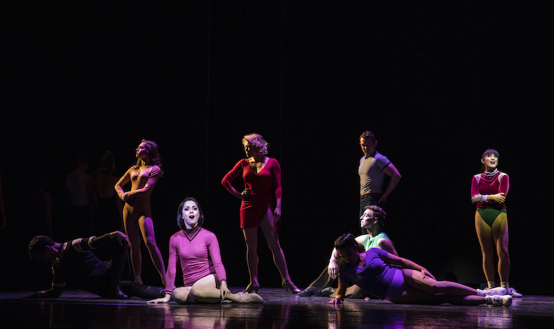 Performers of A Chorus Line pose on stage. Some stand with their arms crossed or on their hips. Other sing out to the audience while sitting on the floor.