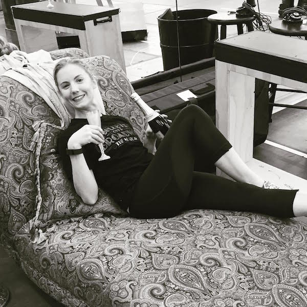 Clare poses on a chaise lounge with a champagne flute and bottle