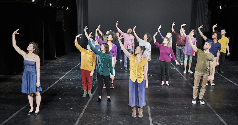 A group of dancers stand en mass in different colored-street clothes. They each outstretch their right arm. Their fingers angle toward them.