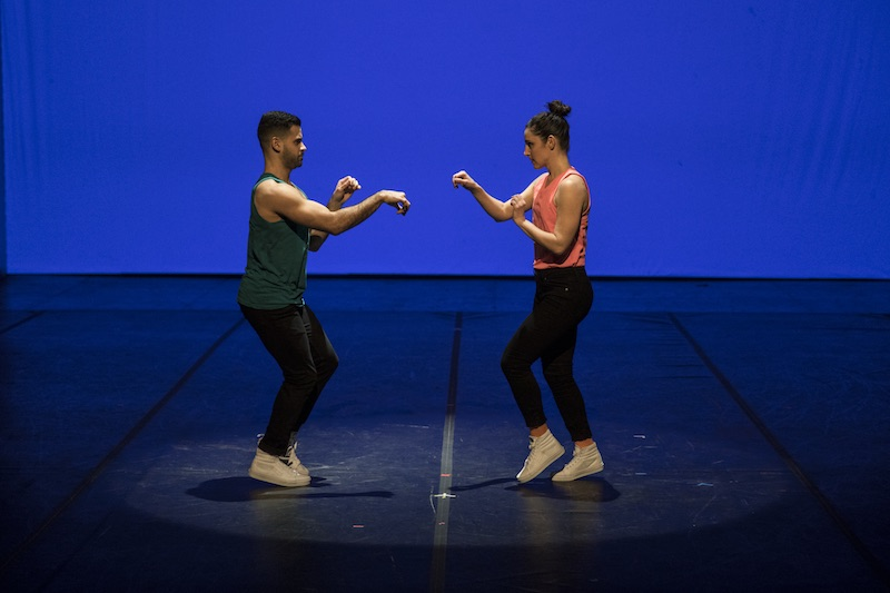 Two dancers in bright colored tanks, jeans and white sneakers stand at one another. They both have their hands positioned by paws.