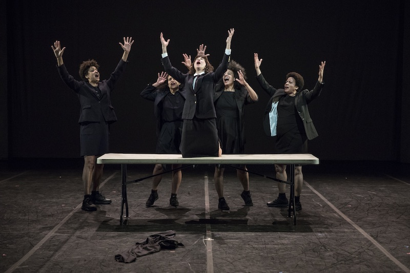 Four women sing around a table with their arms outstretched. Another woman knees atop the table and sings as well.