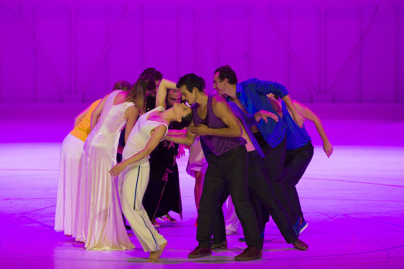 A group of dancers and opera singers huddle in a circle behind a magenta cyclorama background.