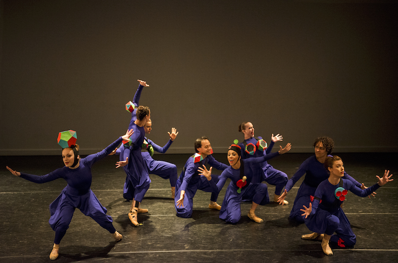 A large group of women in purple unitards with flowy pants. They each wear a cartoonish accessary like an oversized ring as a headpiece.