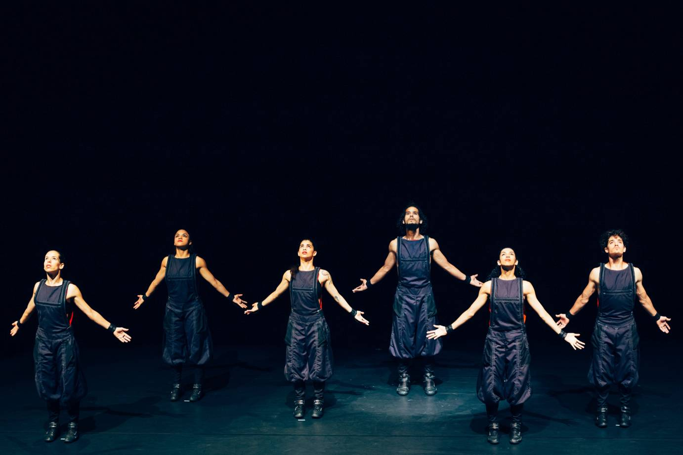 Six dancers extends their arms to the side while looking tough