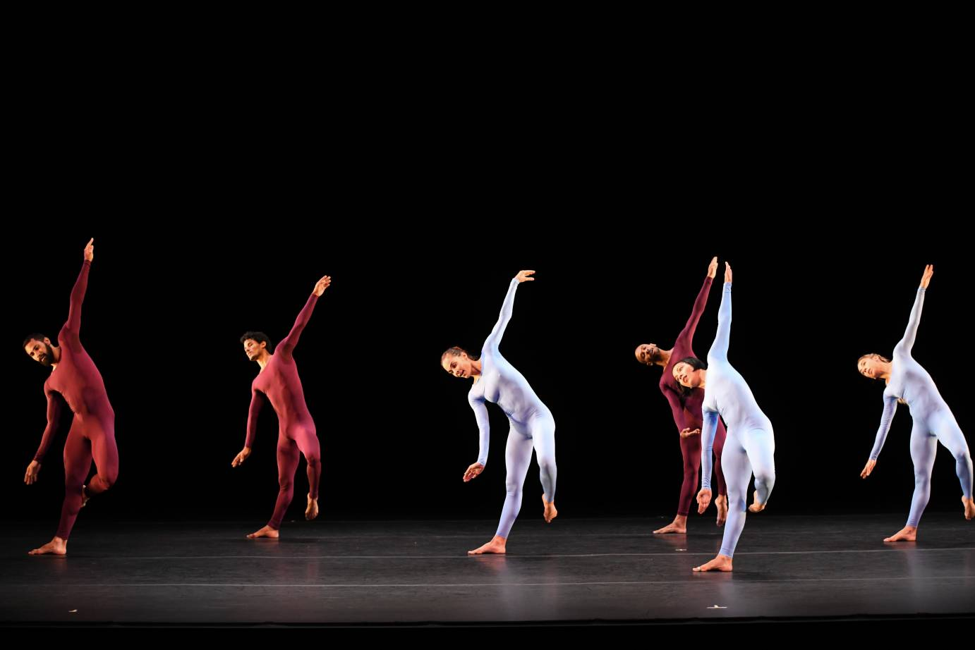Dancers in purplish unitards tip their bodies sideways