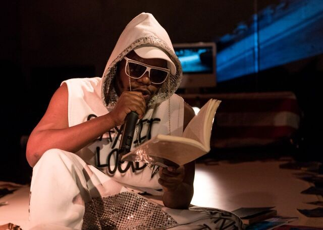 Jaamil Olawale Kosoko wearing a white hoodie and sunglasses while reciting poetry from a book.