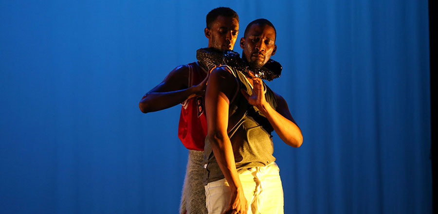 Two dancers on stage, one with his arm wrapped around the other's neck.