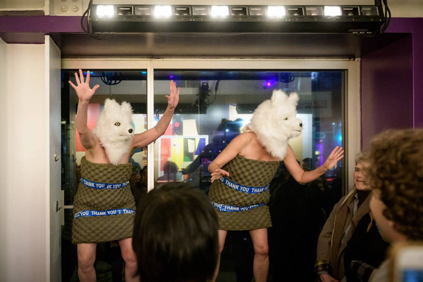 Two women in wolf heads get the crowd going in a theater lobby