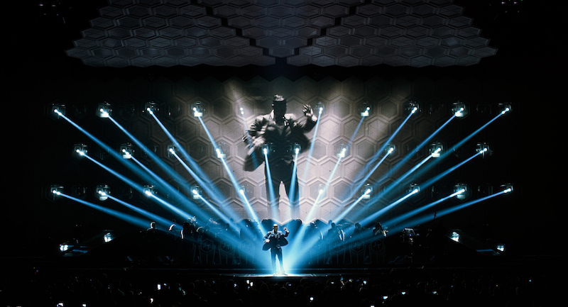 Justin Timberlake with this band the Tennessee Kids on a stage. Blue laser lights fill the stage,