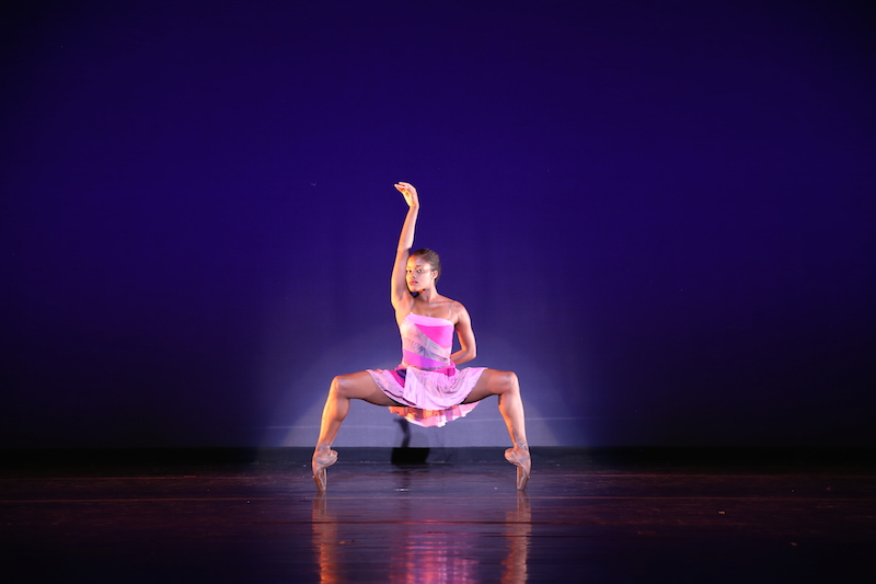 A woman sits in a deep second plie en pointe. Her right arm is outstretched grazing her face.