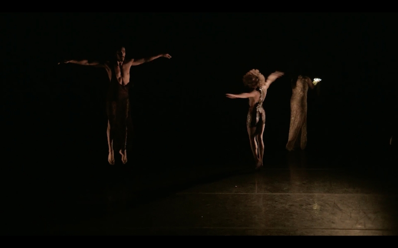 A shirtless man with his arms outstretched in the semi darkness. Another figure with her back to the audience also outstretches her arms