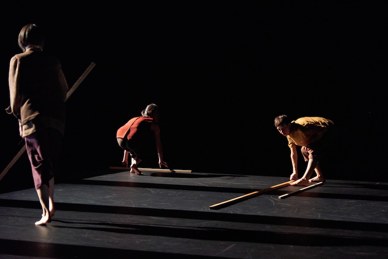Three women in semi darkness hold sticks or lay down the long wooden rods. They cast long shadows.