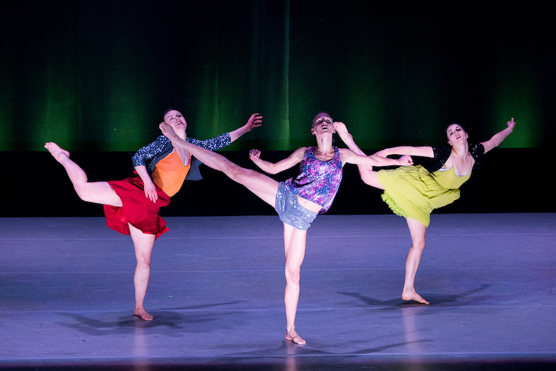 Three women in colorful blouses and skirts lift one of their legs in turned in and contorted positions