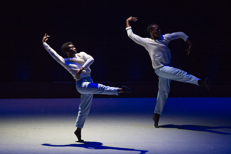 Two dancers in white pants and shirts relve on one leg while their other leg is extended into an air. They slightly arch their backs.