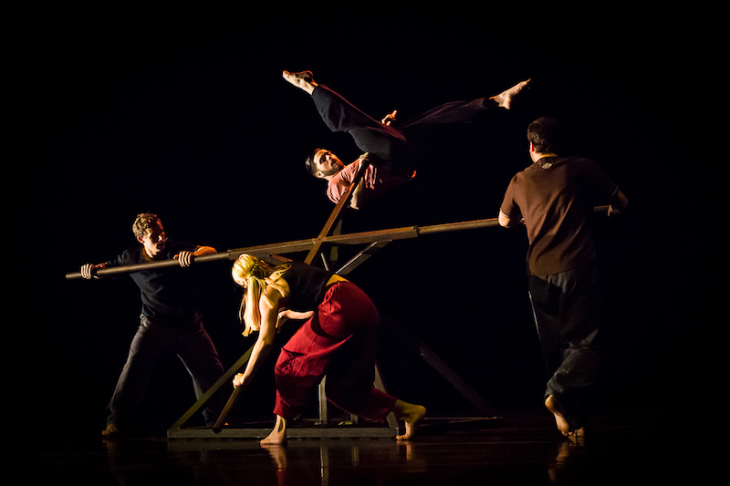 Four dancers surround a geometrically structured wood object. One dancer is in midst of hoisting himself up onto one of the structure's spindles.