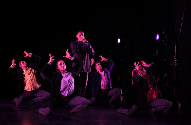 Dancers in black suits and button ups squat to the floor and their arms gesture above their heads as if they were placing a crown on top of their heads. One dancer stands with his hands in front of his mouth.