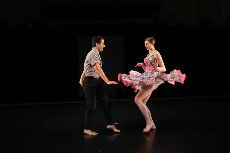 Two dancers do the twist facing one another. Their hands are flexed and they're barefoot. The woman's pink skirt cascades around her as she twists.