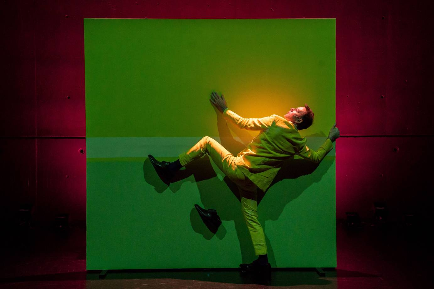 A man in a yellow suit tries to climb a green-lit wall