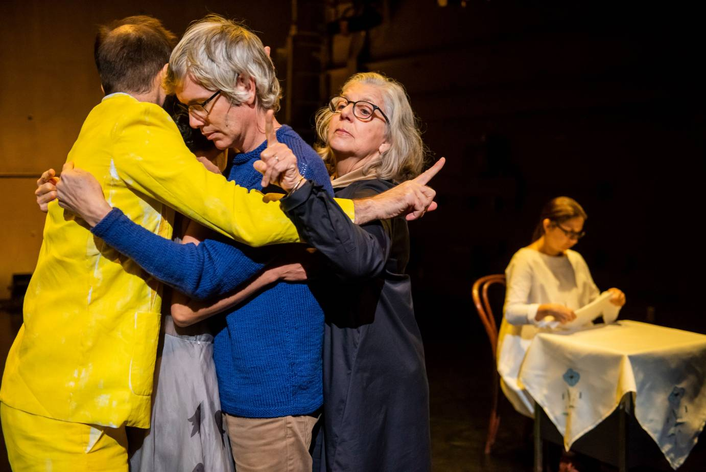 Four performers hug each other as another sits at a table folding a napkin