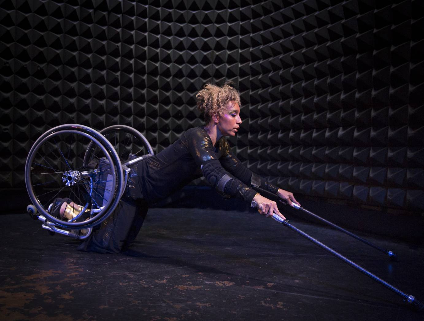 In a wheelchair, a woman balances on her knees. Her arms are extended, and she holds two sticks.
