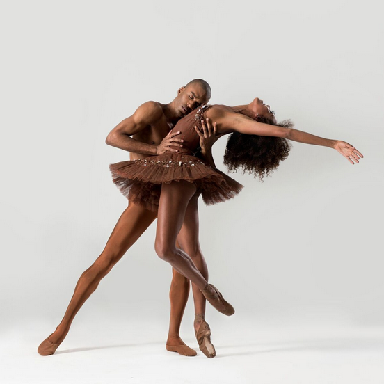 A duet between two DTH dancers. Both are dressed in all-brown.