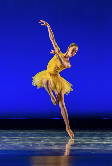 A ballerina in a yellow tutu with one leg raised and the other en pointe.