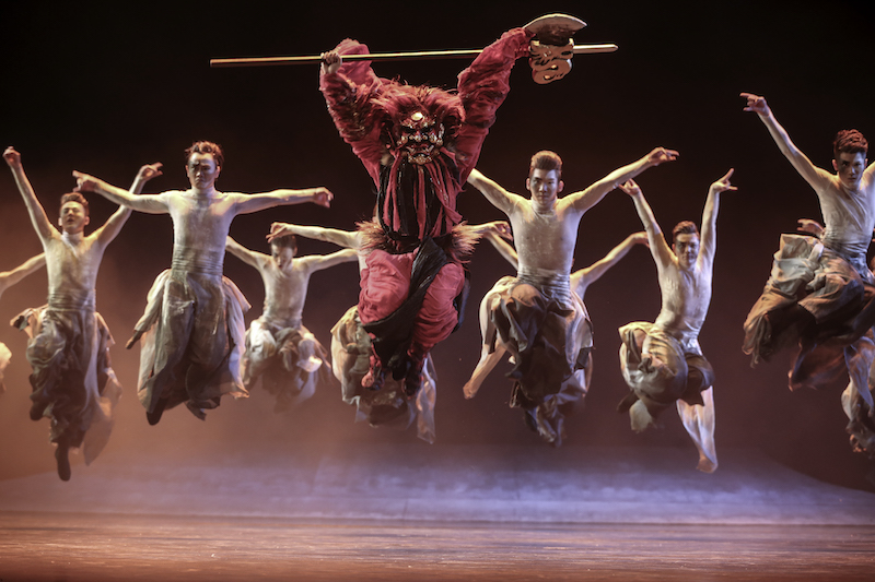 A group of dancers jump in the air. The central figure wheres a red costume and mask and holds a stick over their head.