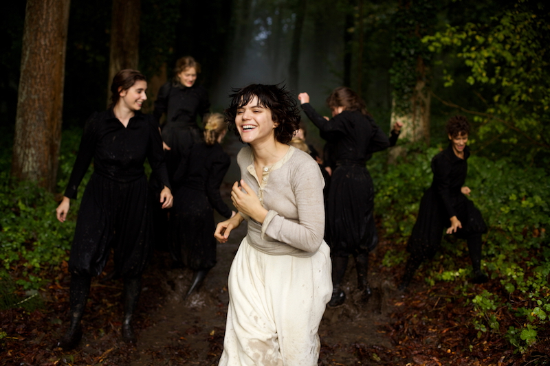 A group of women in black smile and run through the forest. A woman in white leads them.