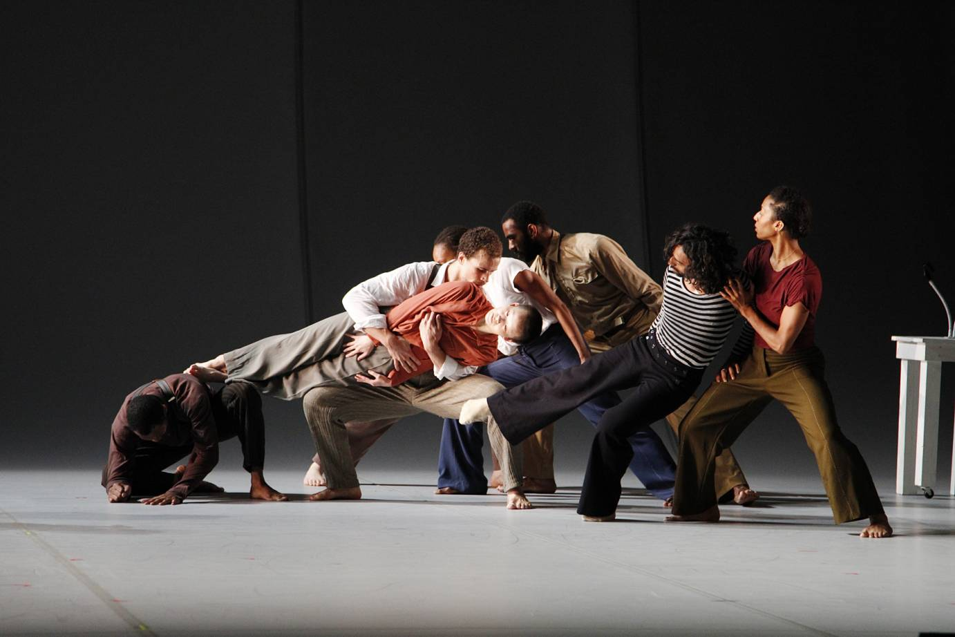 Dancers form a cascading chain with their bodies. They lean on one another. One dancer is held horizontally by the group.