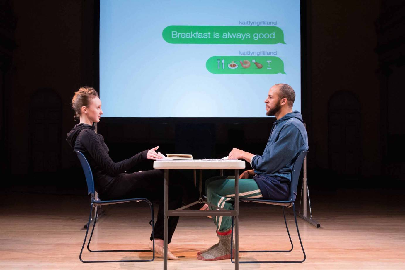 Kaitlyn Gilliland and Will Rawls sitting at a table in #loveyoumeanit with a projection of their text messages in the background.
