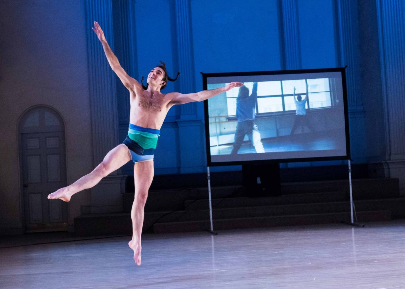 Silas Riener smiling in a leotard while rehearsal footage of him and Adrian Danchig-Waring is projected in the background