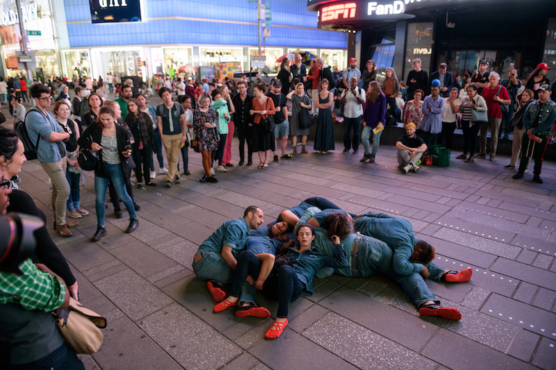 A group of dancers lay on the ground. They wear red shoes and jeans and jean button ups.