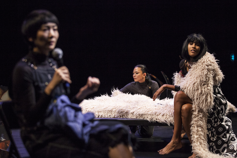 A woman in the foreground holds a mic up to her mouth. Another woman in a fur trimmed rope looks out to the audience. While another performer in the background smoothes a shag blanket that is atop a table.