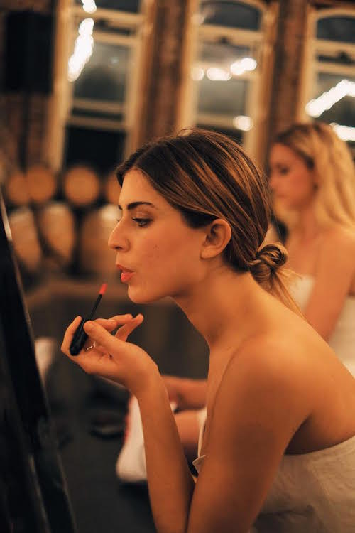 A young debutaunte applies lipstick in the mirror
