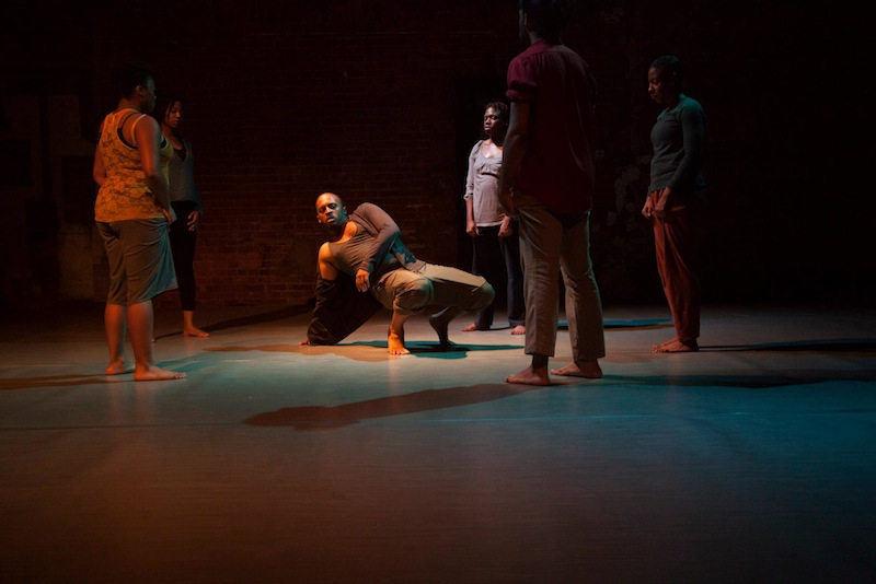 Members of Harge Dance Stories perform in dim lighting. The central male figure is on the floor