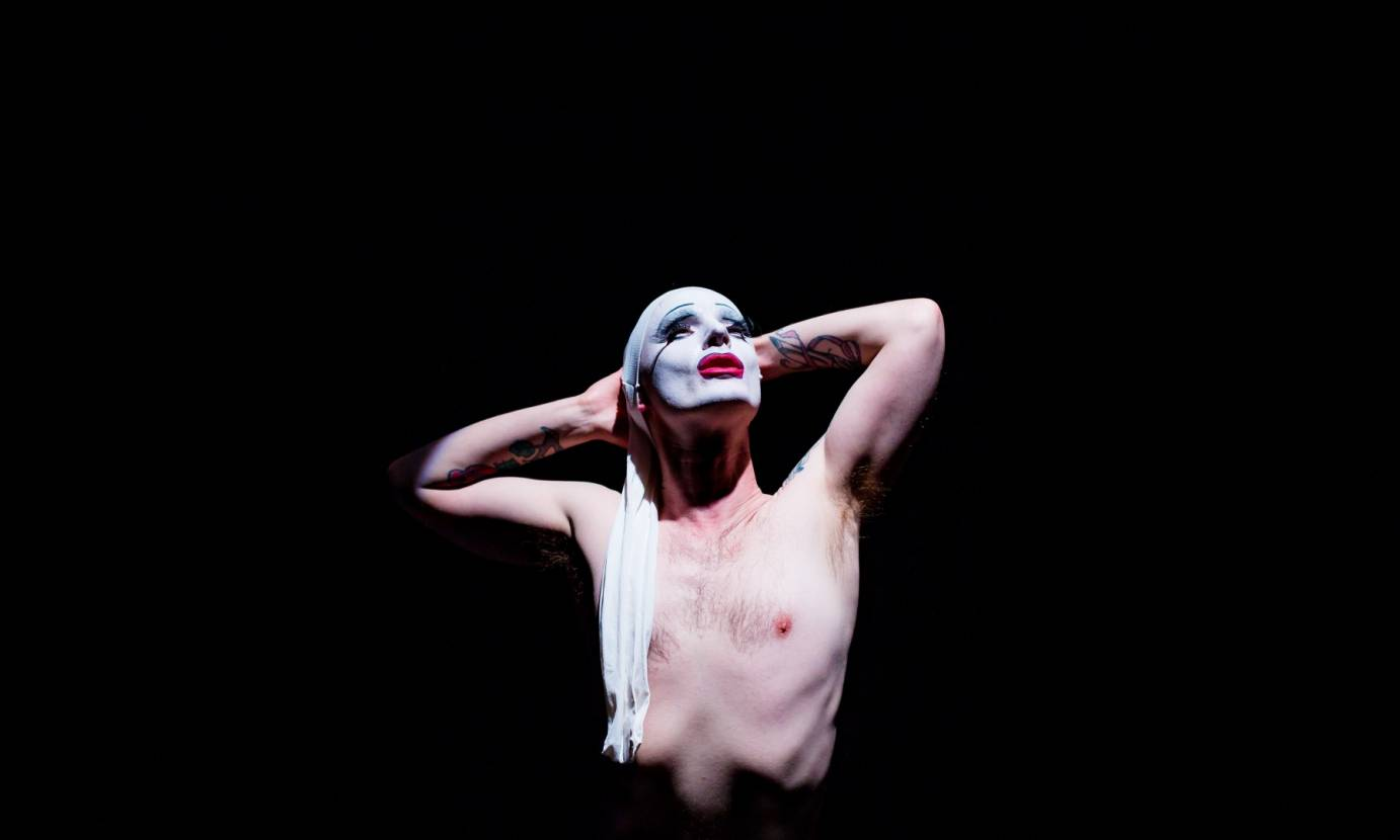 Dickie Beau, shirtless, places his tattoo-ed arm behind his head. His face, painted white with bright red lips, looks up to the stars.