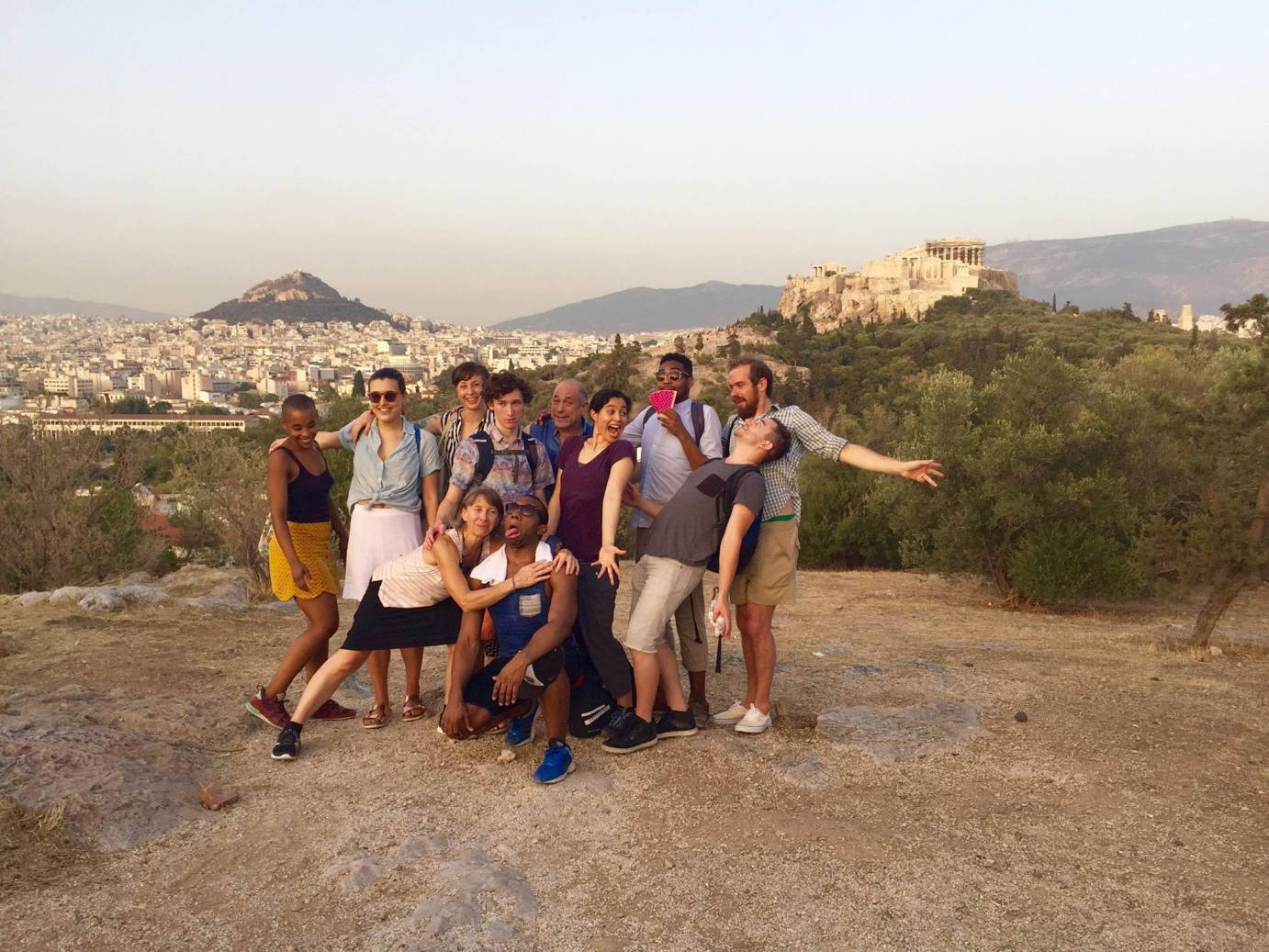 Company members strike silly faces for a photo overlooking the city of Athens