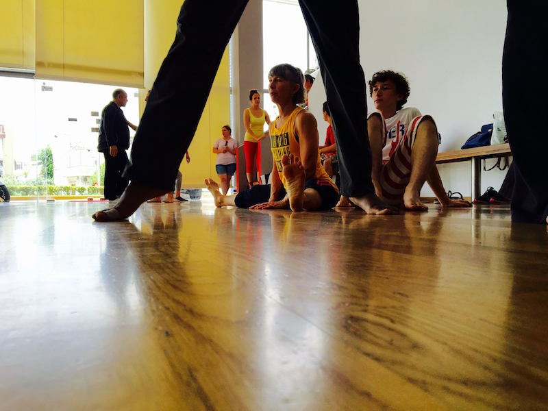 Dancers sit on the floor and stretch in an Athens studio