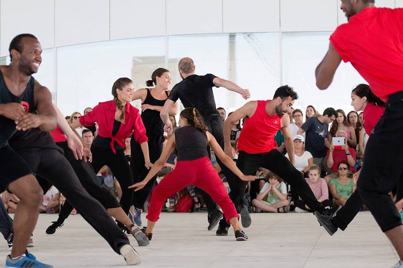 Dancers dressed in black and red smile while dancing in a large group