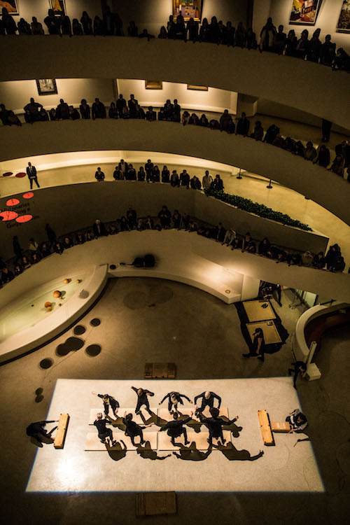 A group of tap dancers tap on wooden boards as audience members peer down  to watch from above on the Guggenheim's various levels
